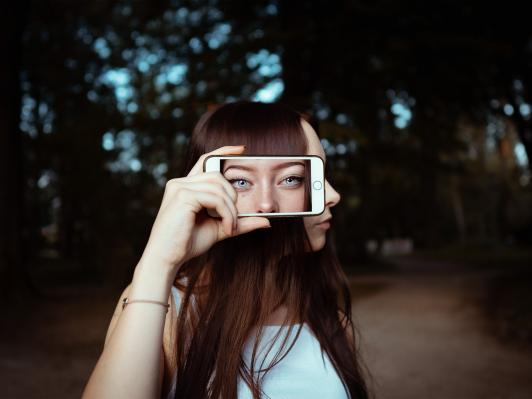 woman holding smartphone with background of woman s face 3887990